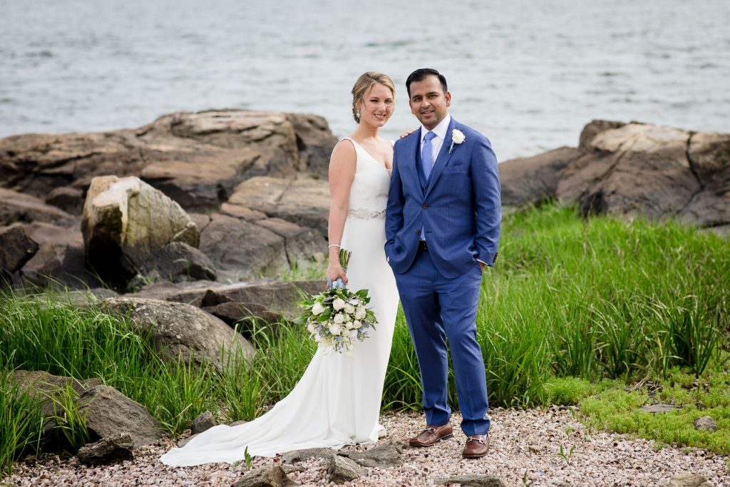 A bride and groom pose for a photo on the beach at their mount hope farm wedding