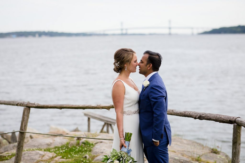A bride and groom kiss in front of the mt hope bridge