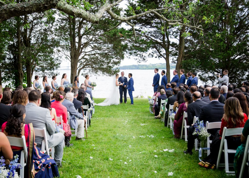 A wedding ceremony by the water at a mount hope farm wedding