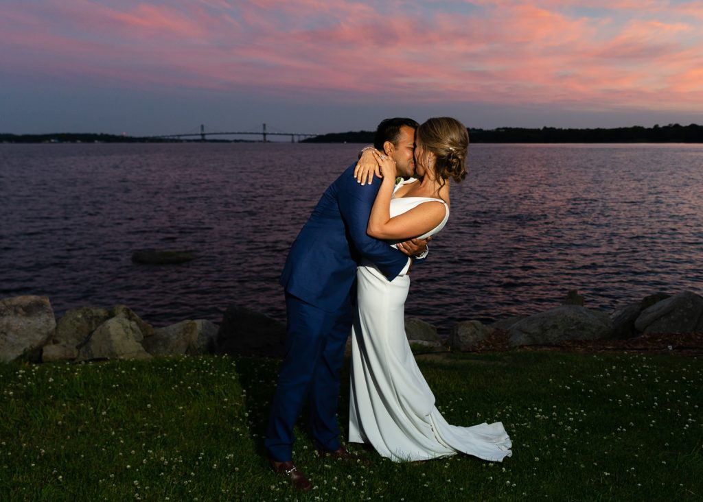 A bride and groom kiss in front of a sunset and the mt hope bridge