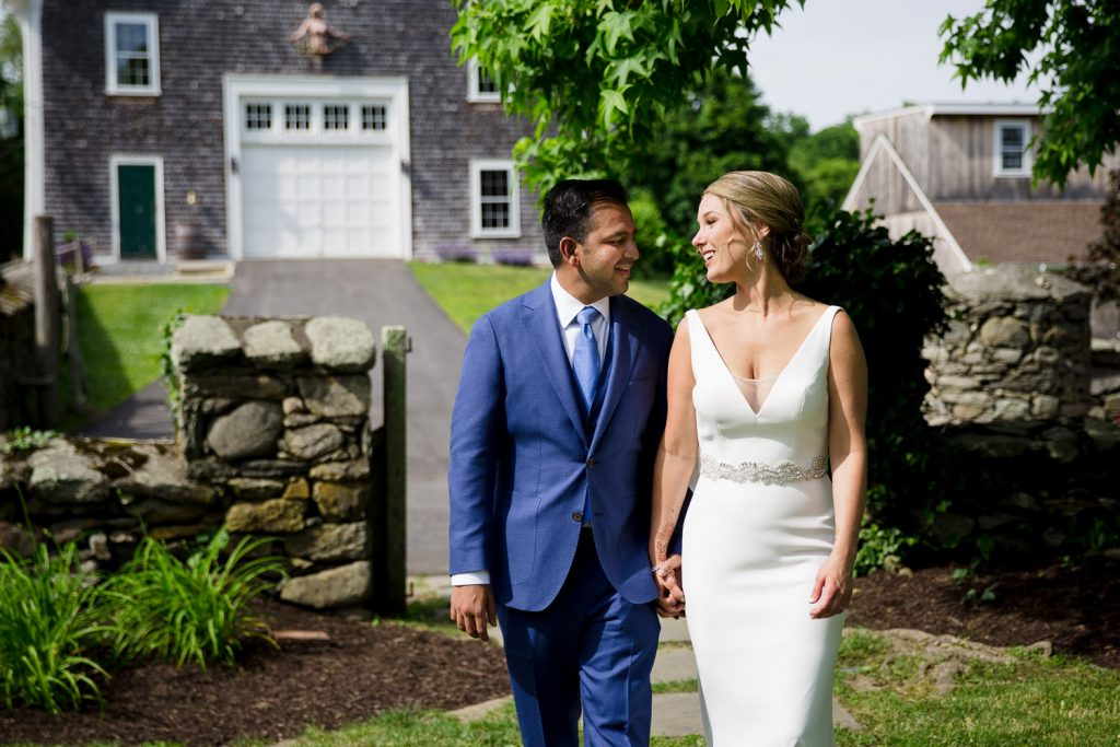 A bride and groom take wedding photos in front of the barn at mount hope farm
