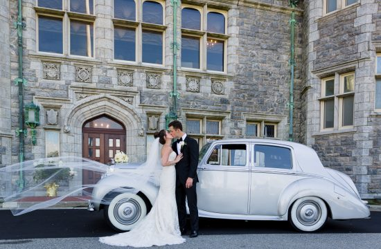 A bride and groom kiss in front of a vintage car and the branford house mansion