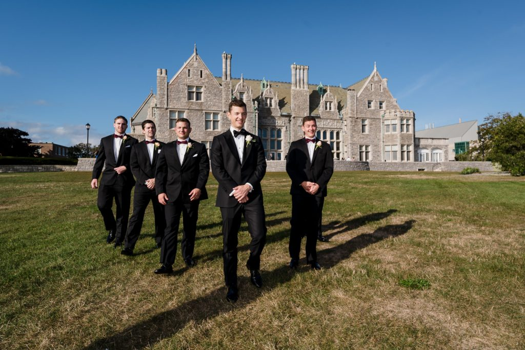 A groom and friends walk across a lawn with the branford house mansion in the background