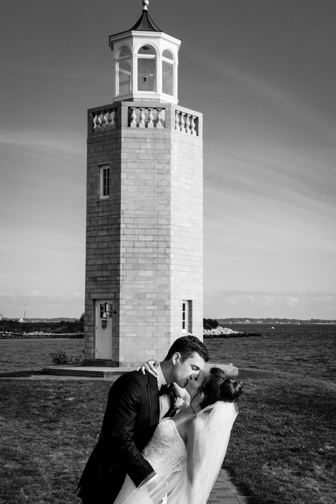A bride and groom kiss along the walkway to the lighthouse at Uconn Avery Point