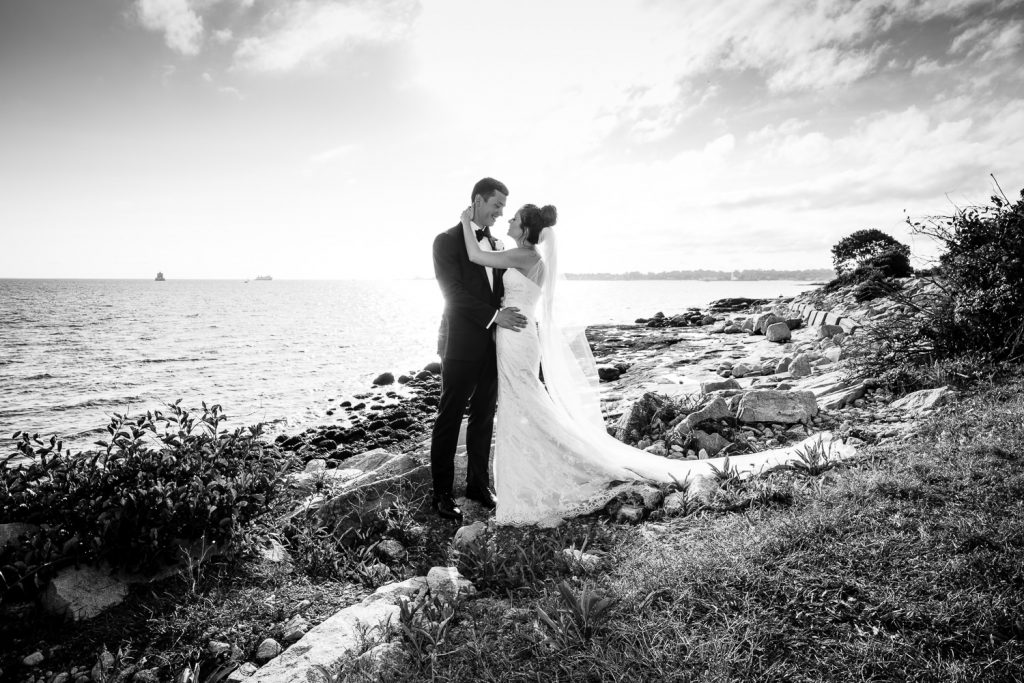 A bride and groom embrace on the rocky beach at branford house avery point