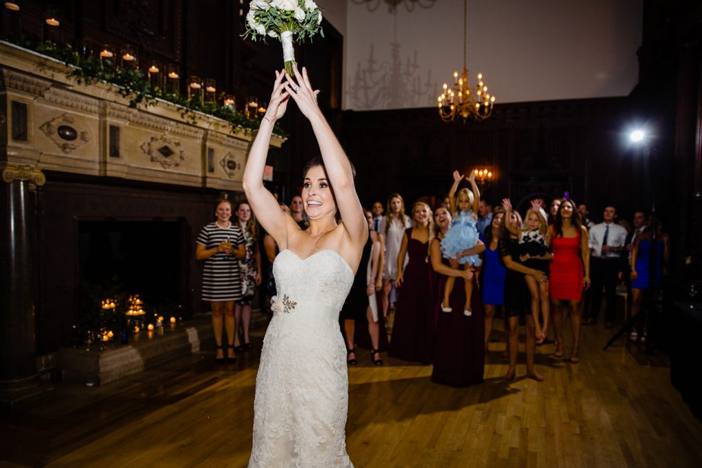 A bride tosses her bouquet in the grand ballroom at branford house