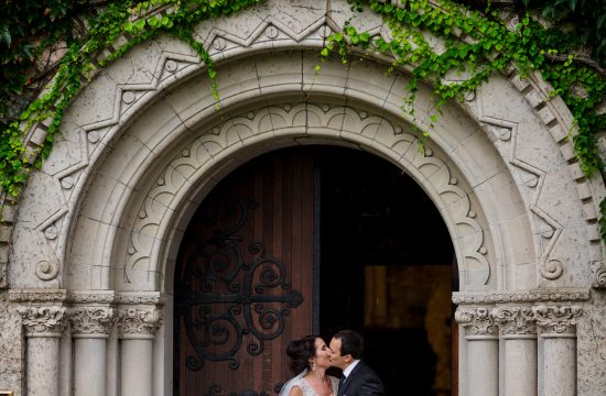 A bride and groom kiss under the arched doorway at the clark chapel before their Mansion at Bald Hill wedding