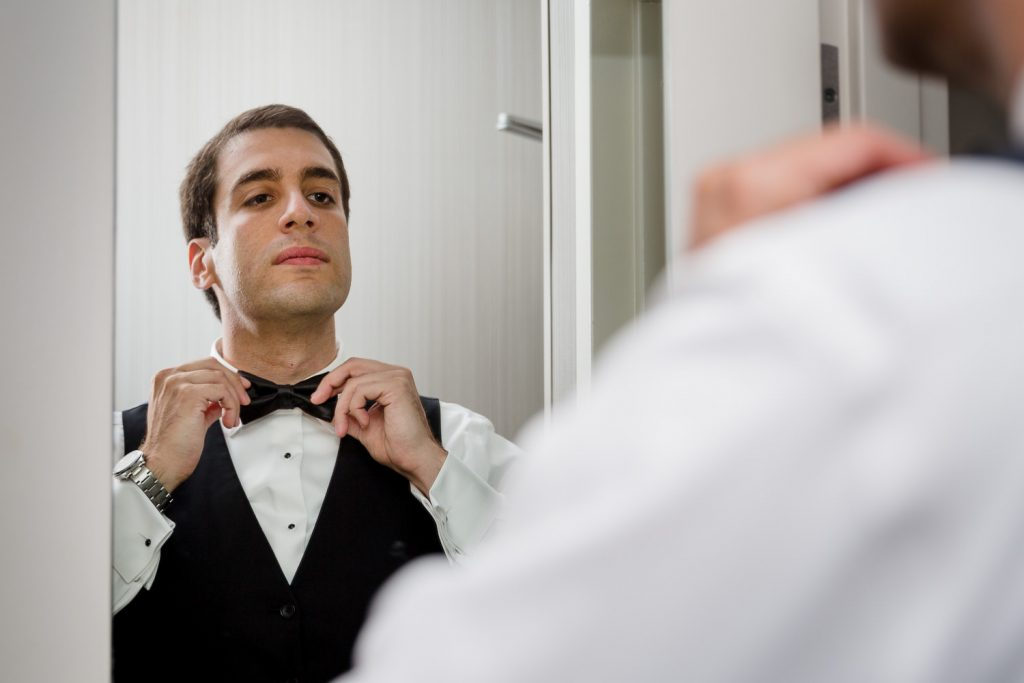 The groom adjusts his bowtie in the mirror at the hotel