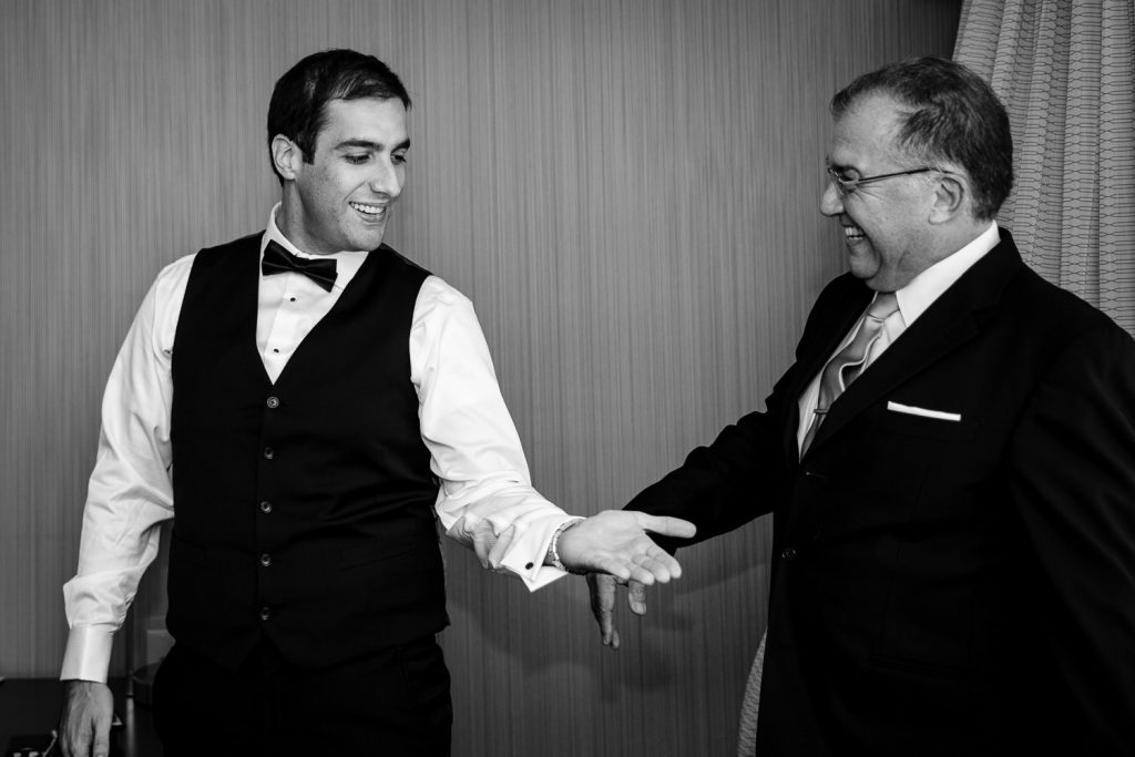 The groom shares a nice moment with his father in the hotel as they get ready for his wedding