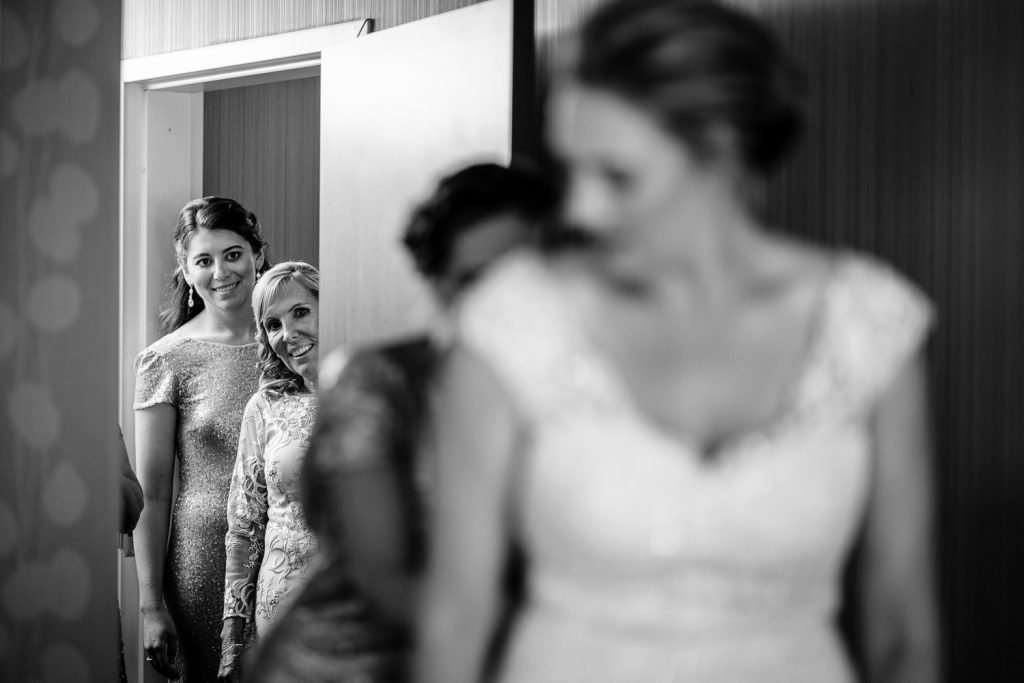 Family looks on with excitement as the bride gets dressed for her wedding