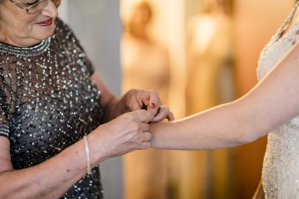 The bride's mother is helping to put a bracelet on her daughter