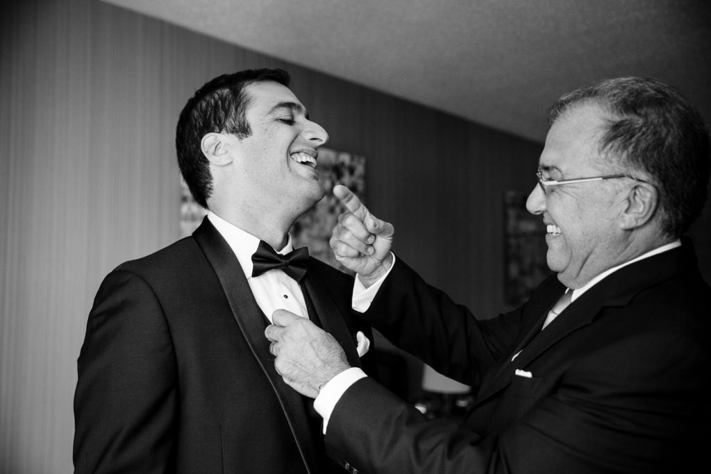 A groom and his father laugh as his father helps him adjust his tuxedo