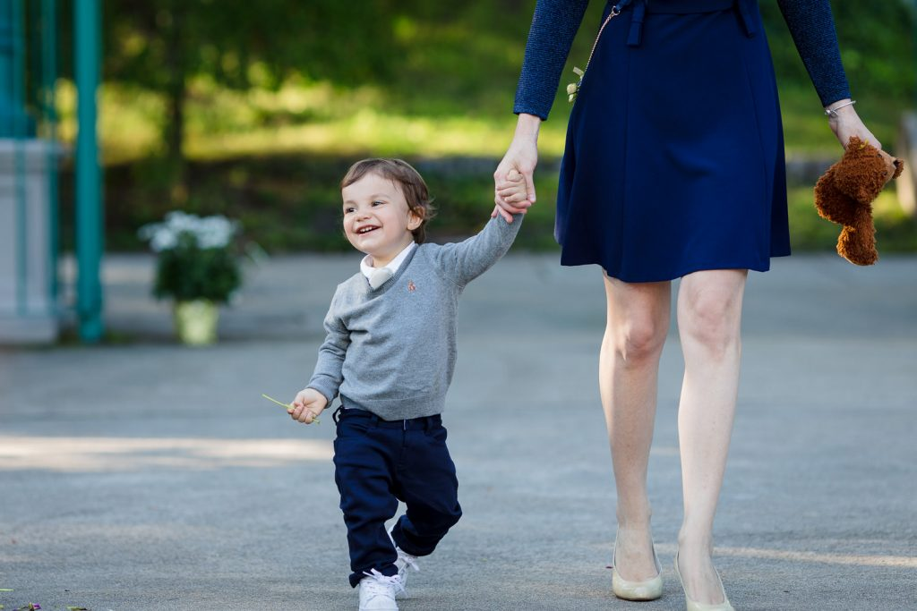 An adorable ring bearer saunters down the aisle holding hands with his mother.