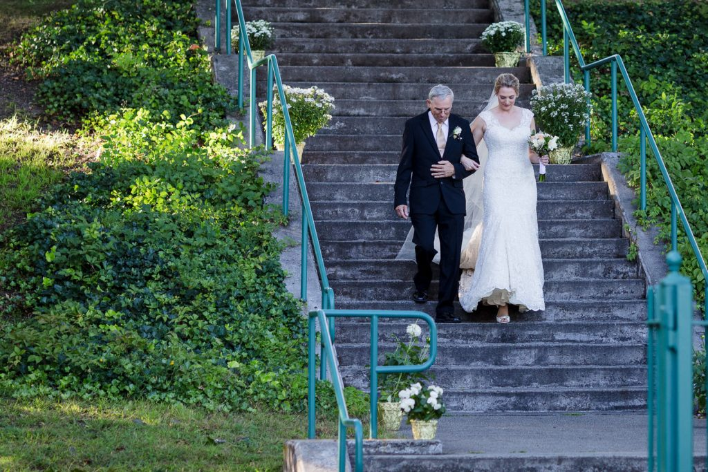 A father walks his daughter down the aisle or stairway to her wedding ceremony at the Roger Williams Park Gazebo