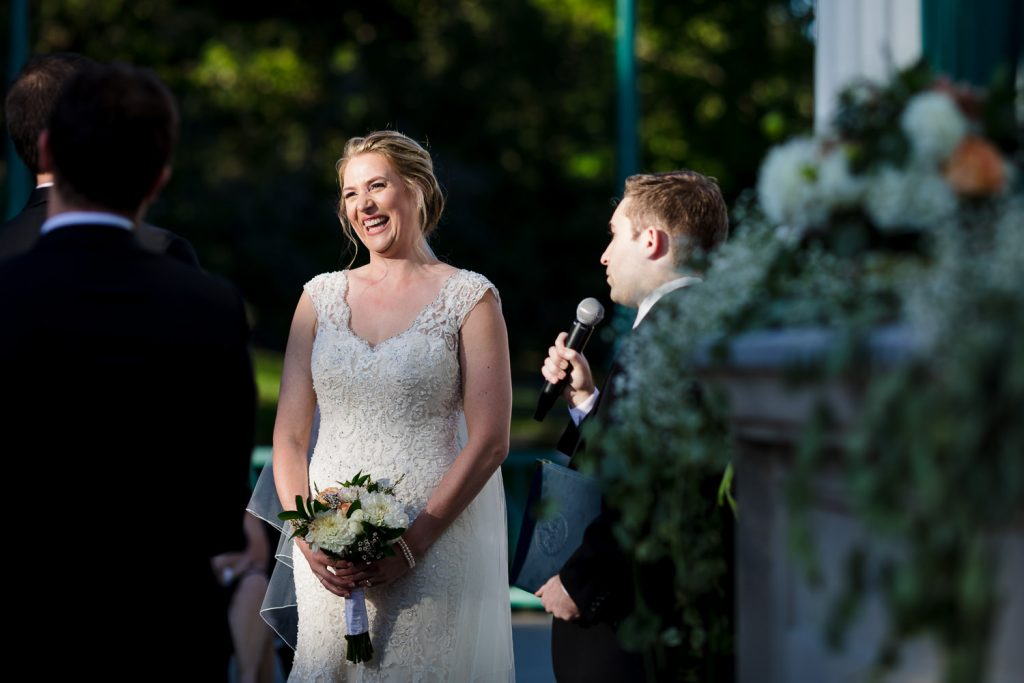 A bride has a huge smile looking at her groom during their wedding ceremony