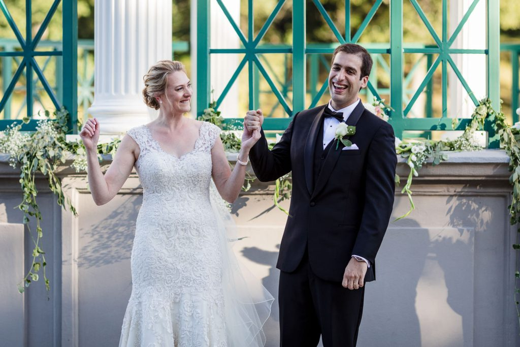 A bride and groom hold hands, smile, and lift their arms triumphantly as they are pronounced man and wife