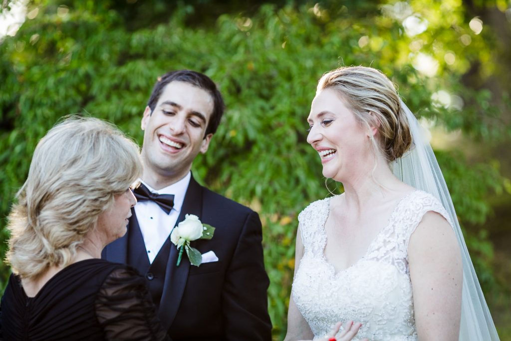A bride and groom joyfully greet a guest after their wedding ceremony