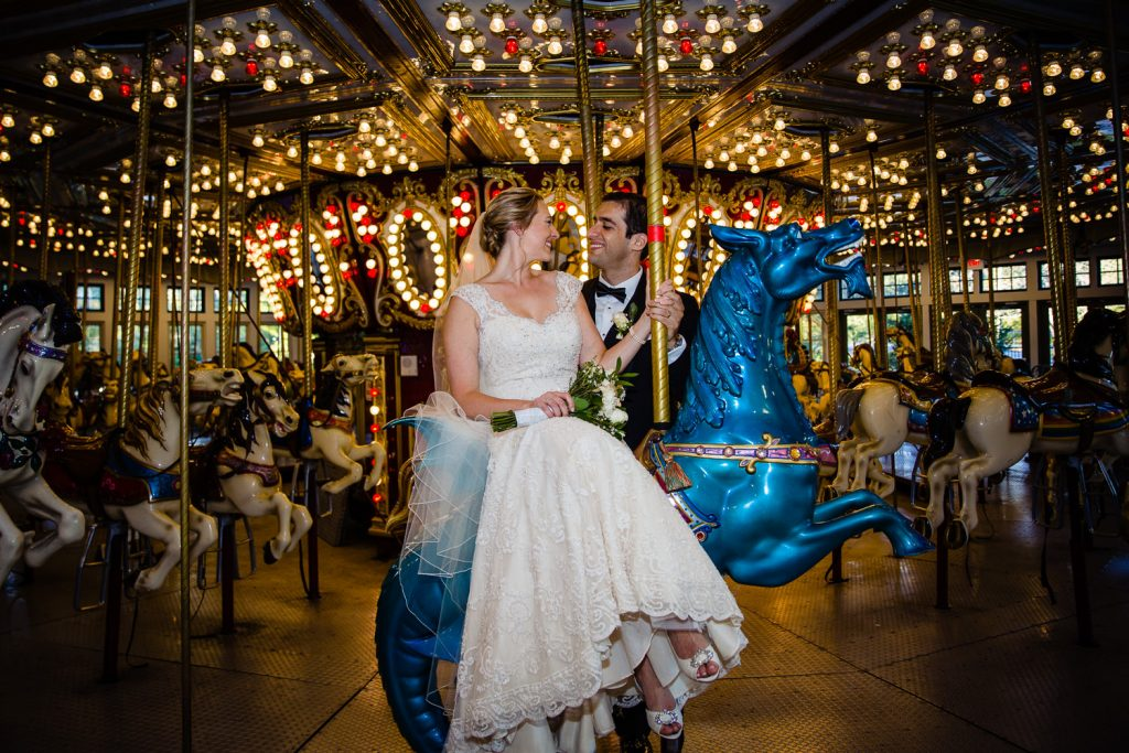 A bride sits on a blue horse and her groom stands behind her while taking photos in the Roger Williams Park casino