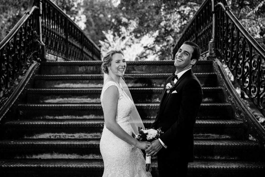 A bride and groom laugh as they try to pose for a wedding photo