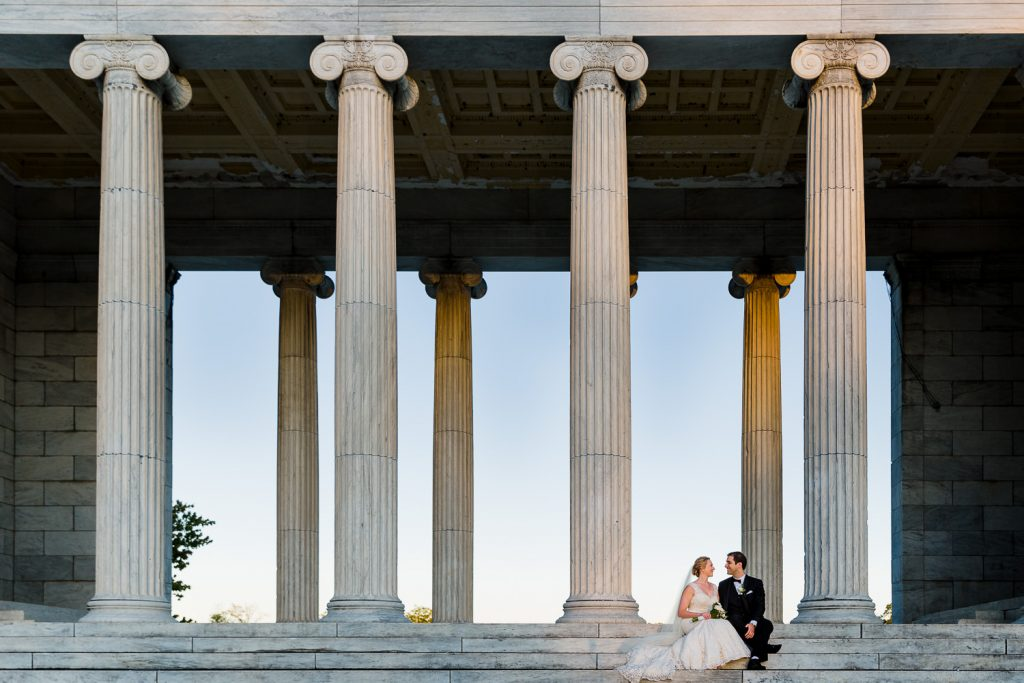 A bride and groom pose for wedding portraits on the steps at the Temple to Music in Roger Williams Park