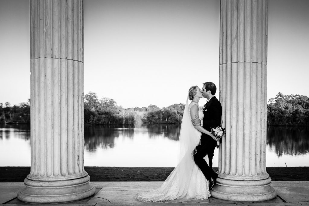 A bride and groom kiss leaning up against one of the columns at the Temple to Music in Providence RI