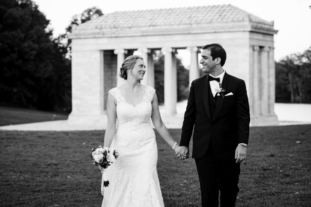 A bride and groom walk hand in hand away from the Temple to Music at Roger Williams Park during their wedding photo session