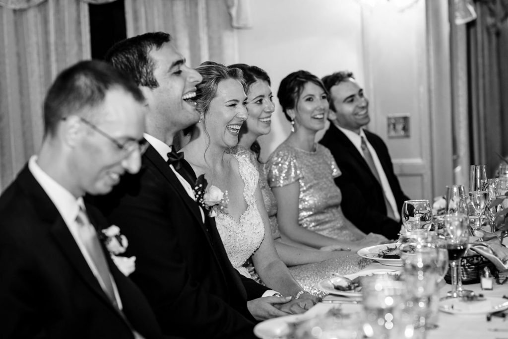 The bride and groom laugh in reaction to a wedding speech as they are surrounded by friends at the head table