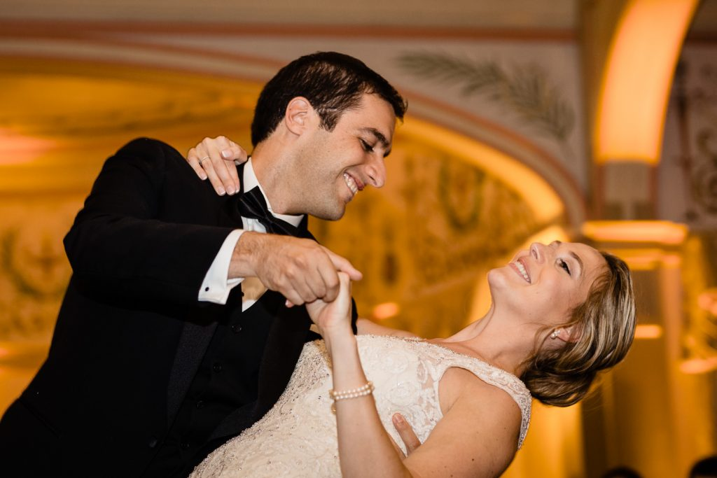 The groom dips his bride during the first dance at their wedding