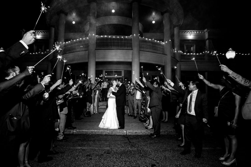 A bride and groom kiss amidst a sea of sparklers outside the Roger Williams Casino at the end of their wedding night