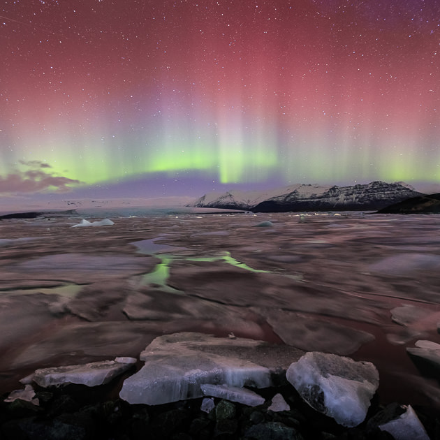 Red and green aurora borealis over the jokulsarlon glacier lagoon in Iceland