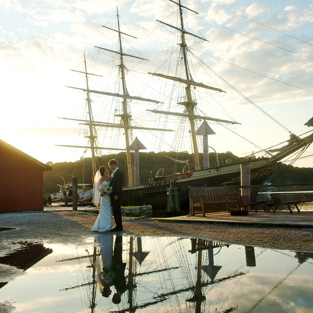 A bride and groom pose for wedding photos amidst the tall ships at Mystic Seaport