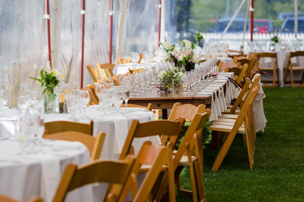Tables set up on the grass under a wedding tent