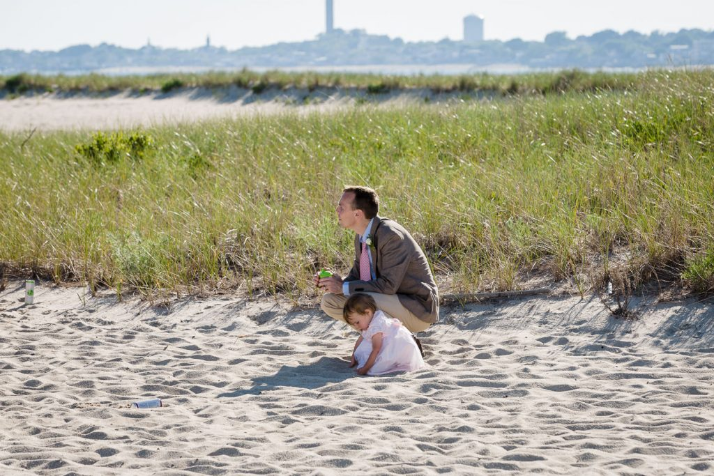 A man and his daughter play in the sand during a cape cod beach wedding with ptown in the background
