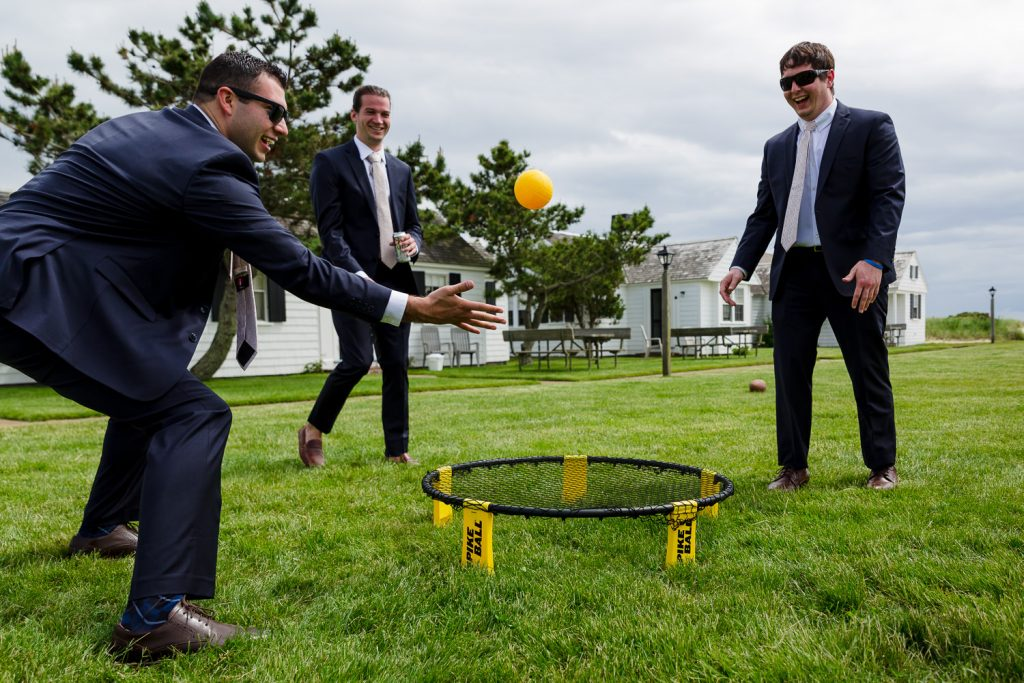 A group of guys in suits play ball on the lawn before a beach wedding