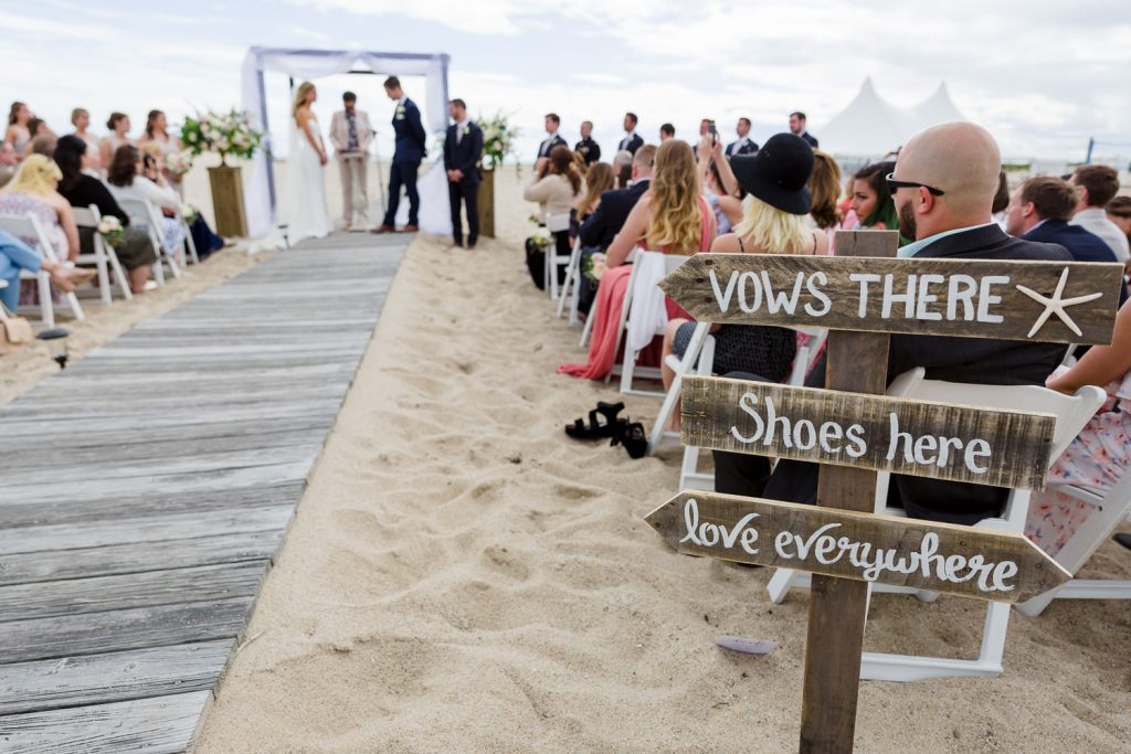 A wedding sign points to a couple getting married on the beach at a kalmar village wedding