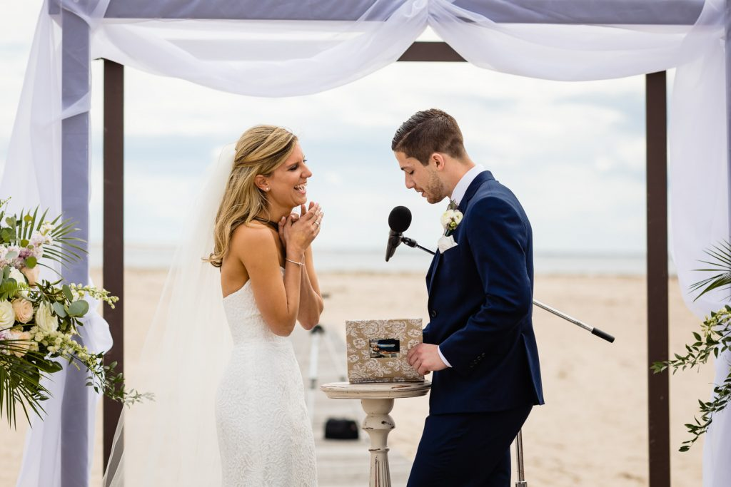 A couple exchanges vows at their cape cod beach wedding
