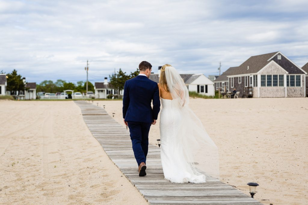 A couple leaves their wedding ceremony on a beach boardwalk in cape cod