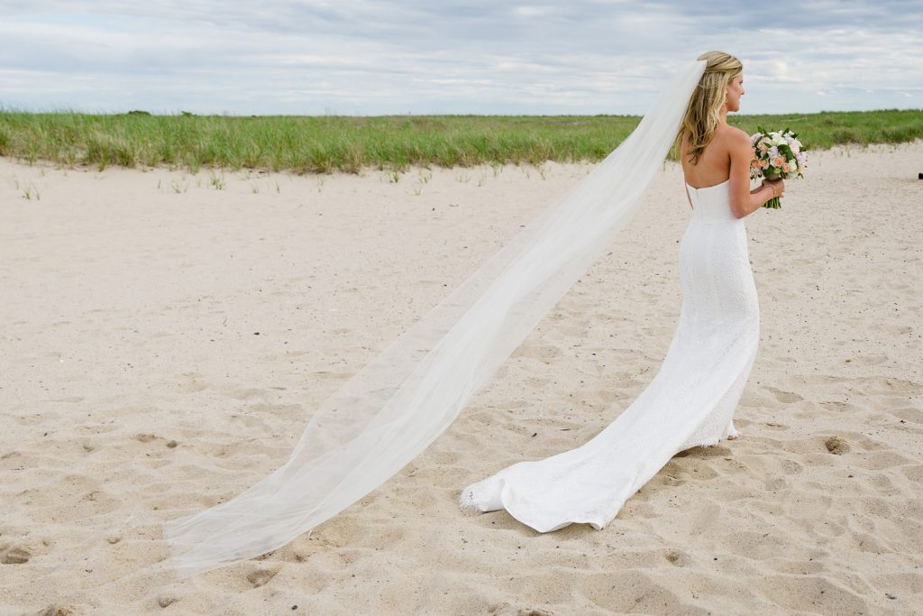 A bride walks along the beach in Truro, MA with her dress and long veil trailing behind her