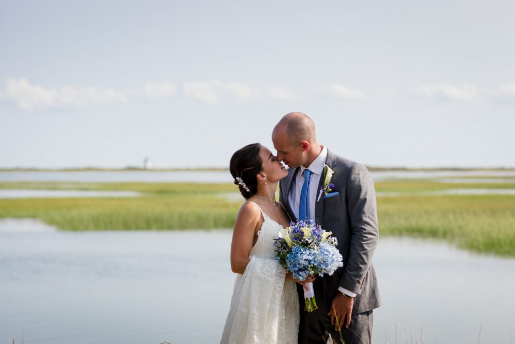 A bride and groom kiss with a beautiful cape cod scene with marsh and lighthouse behind them before their cape cod wedding