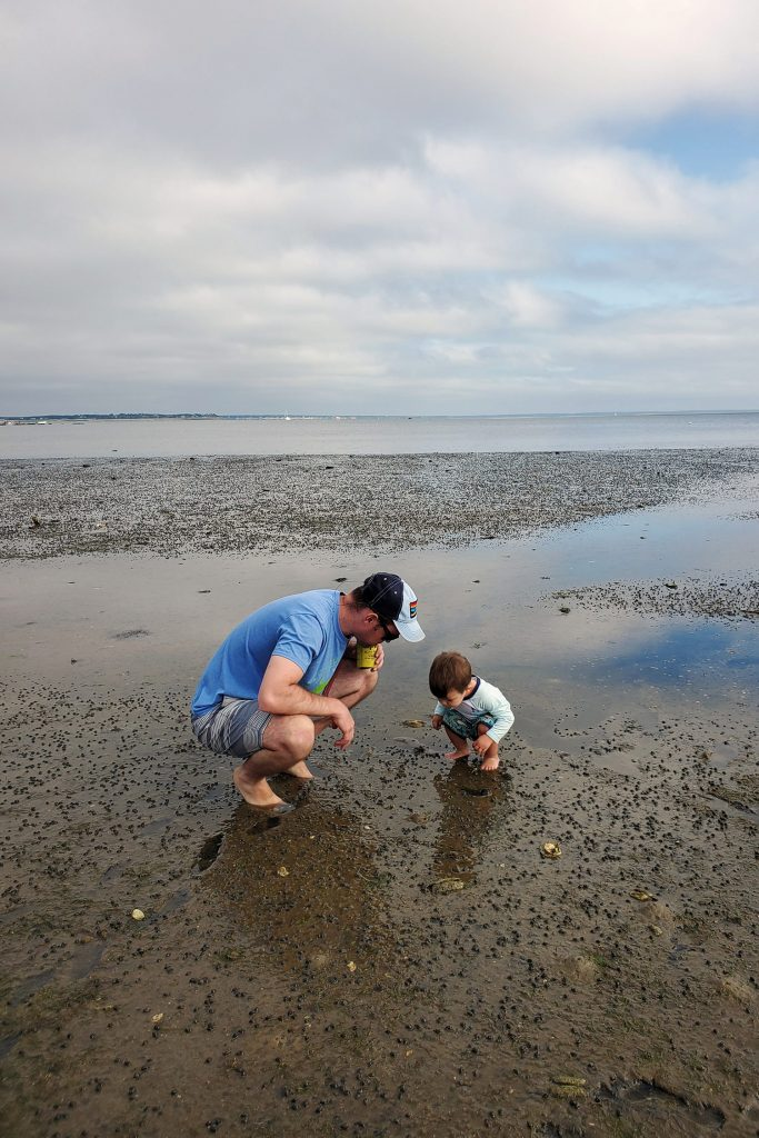 A father and son bend down in tidal flats looking at hermit crabs