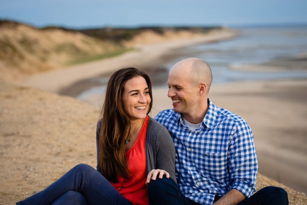 An engaged couple sit on a bluff in wellfleet ma