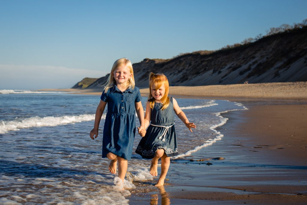 Two young girls hold hands and run through the surf at newcomb hollow beach