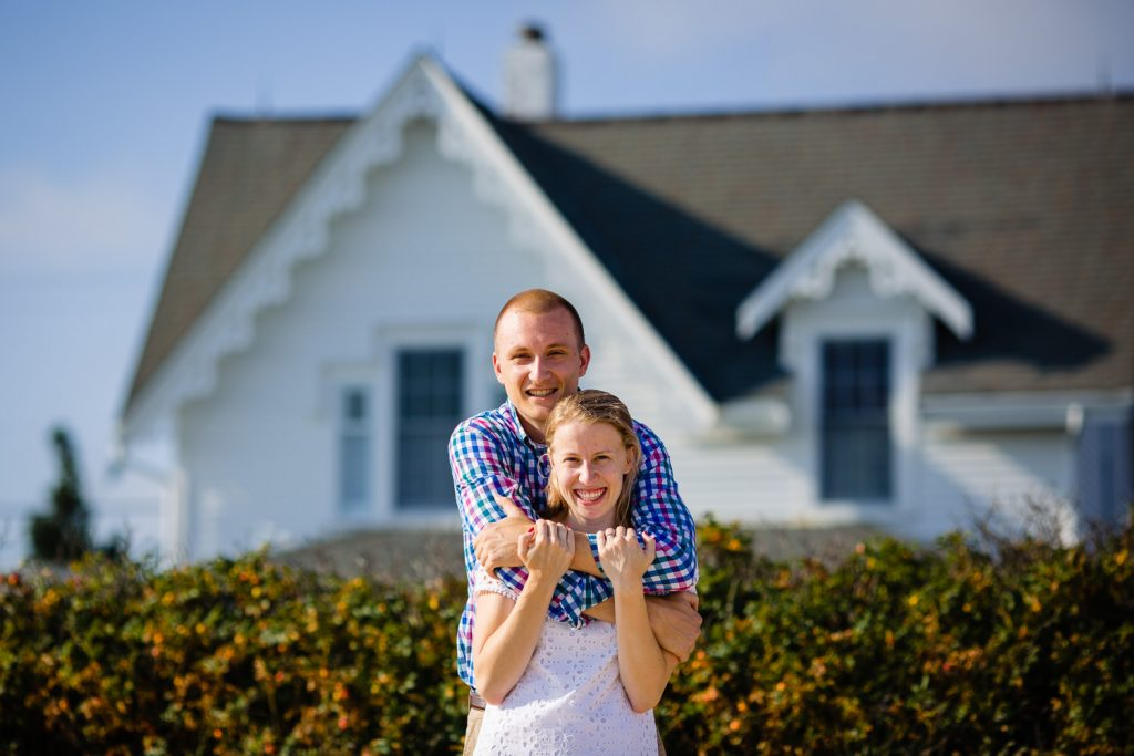 A newly engaged couple hug in front of the old lighthouse keepers house in wellfleet ma