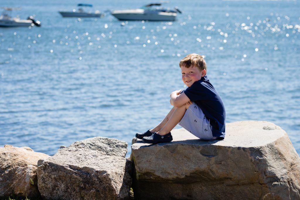 A little boy sits on the rock at bonnet shores taken by a narragansett photographer
