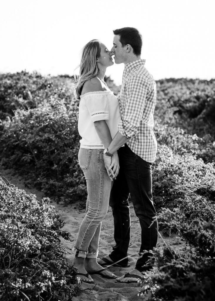 A couple kisses amongst beach roses at fishermans memorial in narragansett