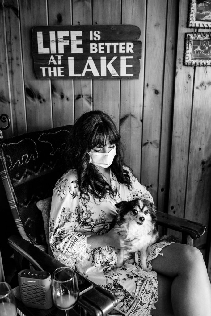 A bride in a mask holds her dog in her lap under a sign that says life is better at the lake