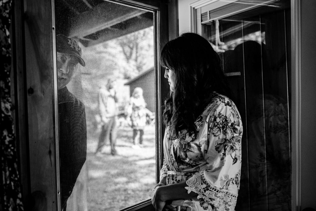 A bride in a robe looks out a screen door as a man looks in