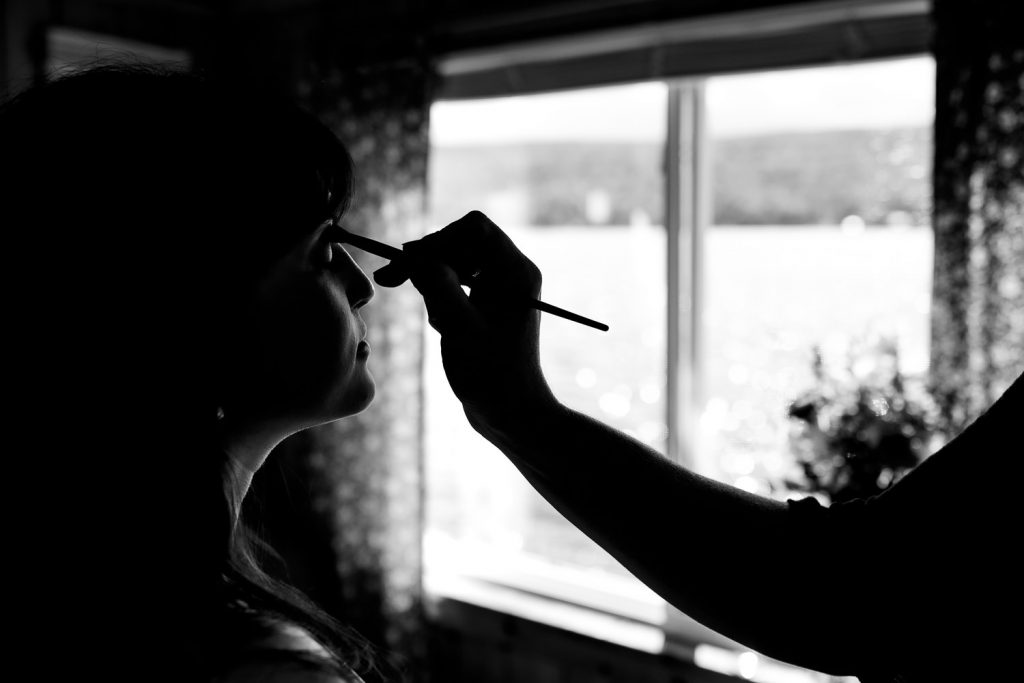 A silhouette of a hand applying makeup to a womans face