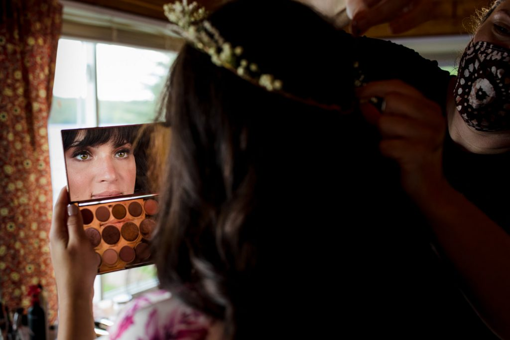 A bride looks in a makeup mirror