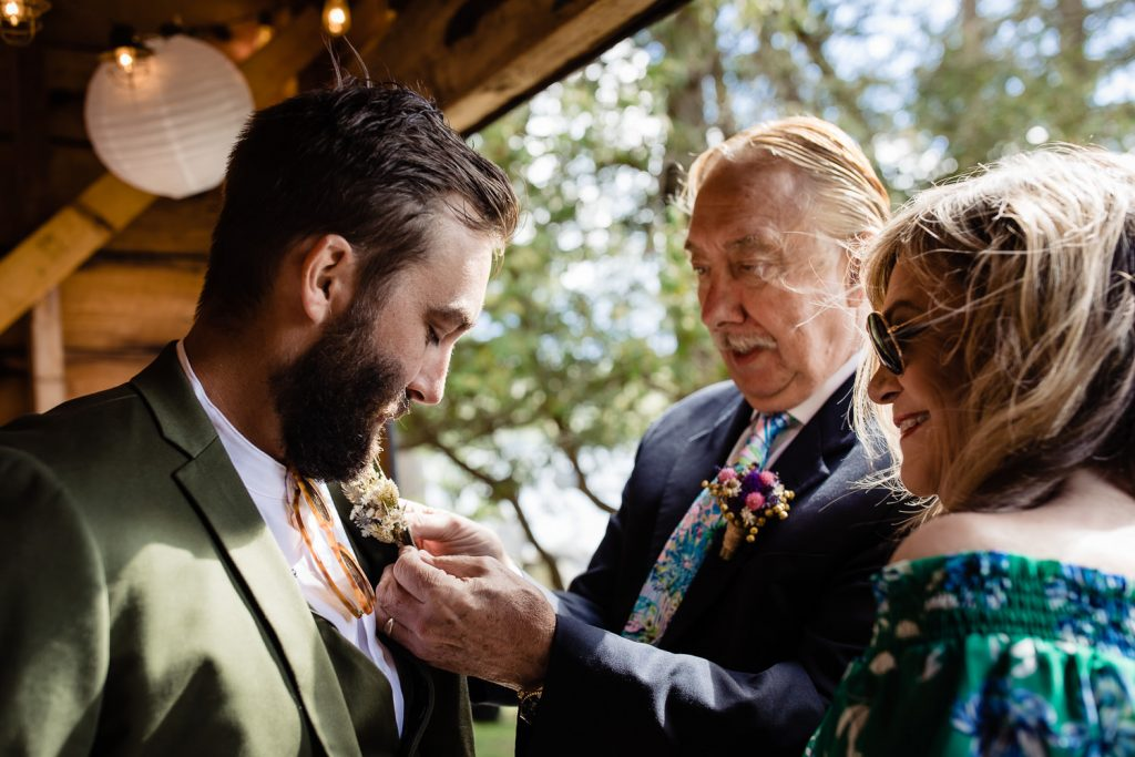 The mother and father of the groom help their son with his boutonierre